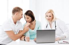 Doktor med patienter som ser bärbara datorn Arkivbild