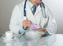 Doktor med pengar arkivfoto