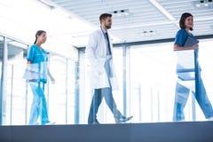 Doktor med sjuksköterskor som går i korridor royaltyfria bilder