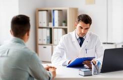 Doktor med skrivplattan och den manliga patienten p? sjukhuset arkivfoton
