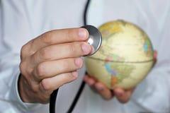 Doktor med stetoskopet och jordklotet i hans händer fotografering för bildbyråer
