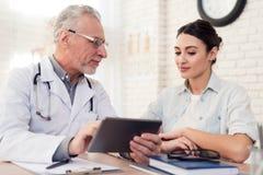 Doktor med stetoskopet och kvinnligpatienten i regeringsställning Doktorn använder minnestavlan royaltyfri foto