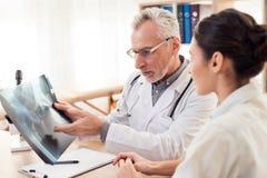 Doktor med stetoskopet och kvinnligpatienten i regeringsställning Doktorn visar röntgenstrålen royaltyfria bilder