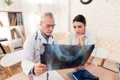 Doktor med stetoskopet och kvinnligpatienten i regeringsställning Doktorn visar röntgenstrålen till patienten arkivbilder
