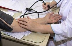 Doktor, medizinische Arbeitskraft in einem weißen Mantel hinter einem Schreibtisch, der b misst Lizenzfreie Stockfotografie