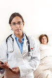 Doktor mit älterem Patienten im Hintergrund Stockfotografie