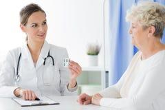 Doktor mit dem Stethoskop, das Pillen gibt stockfotografie