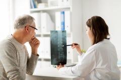 Doktor mit Dornröntgenstrahl und älterer Mann am Krankenhaus lizenzfreies stockbild