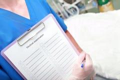 Doktor mit einem Klemmbrett in einem Krankenhaus Lizenzfreie Stockfotos