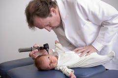 Doktor mit einem neugeborenen Schätzchen Lizenzfreies Stockfoto