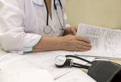Doktor mit einem Stethoskop und einem Manometer sitzt an einem Tisch und Stockbilder
