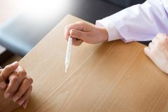 Doktor mit einem Thermometer in seiner Hand, die geduldiges ` s im hospit nimmt Lizenzfreie Stockfotos