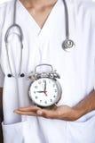 Doktor mit einer Alarmuhr Lizenzfreies Stockbild