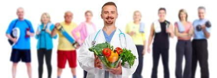 Doktor mit Gemüse und Gruppe Eignungsleuten lizenzfreie stockbilder