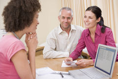 Doktor mit Laptop und Paaren im Büro des Doktors Stockfotografie