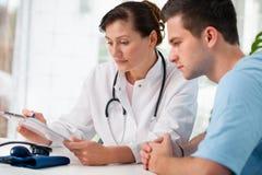 Doktor mit männlichem Patienten stockbild