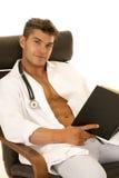 Doktor mit offener Jacke mit Buchsitzenblick Lizenzfreies Stockbild