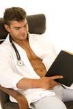 Doktor mit offener Jacke sitzen gelesen Lizenzfreie Stockfotos