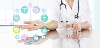 Doktor mit Pillen in der Hand und farbigen Ikonen Stellen Sie schützende Schablone und die Pille gegenüber, die im Hintergrund ve Lizenzfreie Stockfotografie