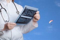 Doktor mit Röntgenstrahlbild in den Händen auf einem defocused Hintergrund Se Stockfotografie
