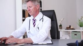 Doktor mit Stethoskop um seins, das am Laptop neckworking und Kamera betrachtet worden sein würden stock footage
