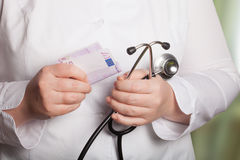 Doktor mit Stethoskop und Geld auf einem unscharfen Hintergrund Lizenzfreie Stockbilder