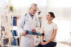 Doktor mit Stethoskop und weiblichem Patienten im Büro Doktor zeigt Röntgenstrahl von Hüften lizenzfreies stockbild