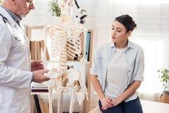 Doktor mit Stethoskop und weiblichem Patienten im Büro Doktor zeigt skeleton ` s Hand stockfoto