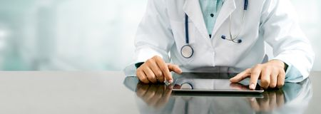 Doktor mit Tablet-Computer im Krankenhausbüro stockfotografie