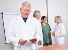 Doktor mit Tablettencomputer und -team Stockfoto