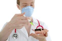 Doktor mit vaccine Spritze der Grippe und Spielzeugschwein Lizenzfreie Stockfotos