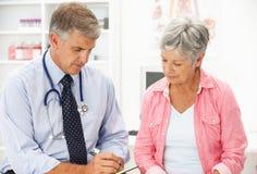 Doktor mit weiblichem Patienten Stockfotos