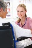 Doktor mit weiblichem Patienten stockbild