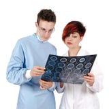 Doktor mit zwei Jungen, der Tomographieergebnis betrachtet Stockfotografie