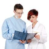 Doktor mit zwei Jungen, der Tomographieergebnis betrachtet Stockbilder