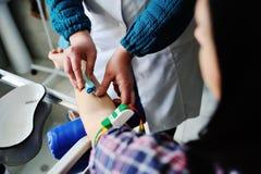 Doktor nimmt Blut von einer Ader bei dem Patienten Stockbild