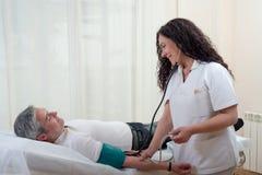 Doktor nimmt dem Patienten das Druckblut, der in Bahre ausgedehnt wird lizenzfreies stockfoto