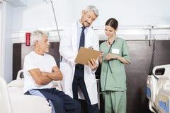 Doktor And Nurse Communicating über Bericht durch älteren Patienten lizenzfreie stockfotos