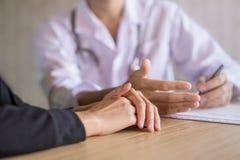 Doktor och kvinnlig patient som i regeringsställning talar att diskutera om examen på ett sjukhus arkivfoto