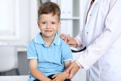Doktor och patient i sjukhus Lycklig pys som har gyckel, medan undersökas med stetoskopet sjukvård och arkivbild