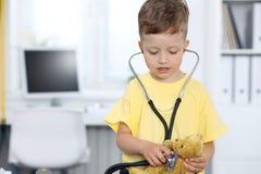 Doktor och patient i sjukhus Lycklig pys som har gyckel, medan undersökas med stetoskopet sjukvård och royaltyfri bild
