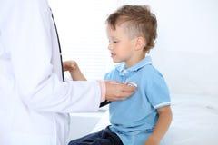 Doktor och patient i sjukhus Lycklig pys som har gyckel, medan undersökas med stetoskopet sjukvård och royaltyfri foto