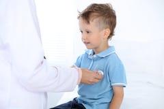 Doktor och patient i sjukhus Lycklig pys som har gyckel, medan undersökas med stetoskopet sjukvård och royaltyfri fotografi
