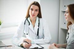 Doktor och patient i sjukhus Rekord för historia för läkarepåfyllningläkarbehandling, medan tala med den unga kvinnan arkivbilder