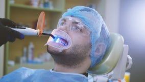 Doktor och patient med retractoren i det tand- kontoret och att göra ren med ultraviolett ljus och den orange skyddande skärmen fotografering för bildbyråer