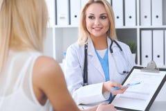 Doktor och patient som diskuterar något medan läkare som pekar in i form för medicinsk historia på skrivplattan arkivbild