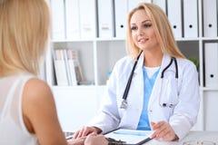 Doktor och patient som diskuterar något, medan sitta på tabellen på sjukhuset Medicin- och hälsovårdbegrepp arkivbild