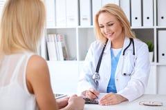 Doktor och patient som diskuterar något, medan sitta på tabellen på sjukhuset Medicin- och hälsovårdbegrepp royaltyfria foton