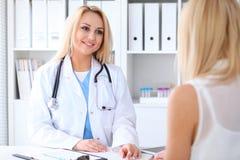 Doktor och patient som diskuterar något, medan sitta på tabellen på sjukhuset Medicin- och hälsovårdbegrepp arkivfoton