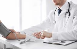 Doktor och patient som mäter blodtryck arkivfoton